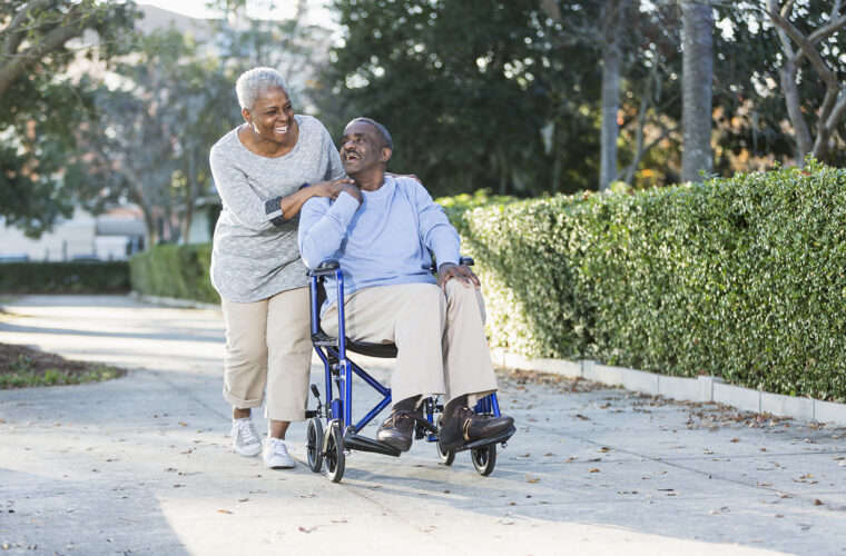woman pushing her husband in a wheelchair