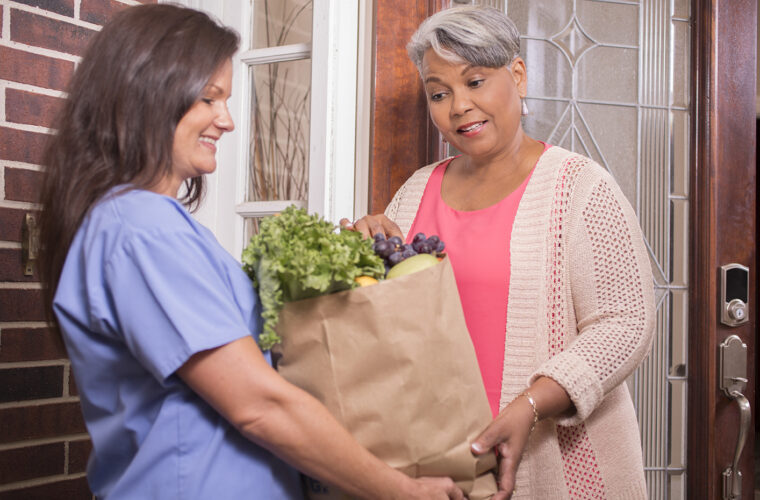 woman receives groceries at home.