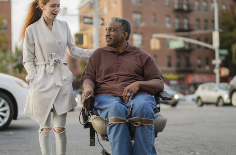 The White teenager girl talking with disabled wheel-chaired African American man when they walking on the street in Bronx, New York, together
